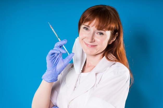 Een vrouwelijke arts glimlacht met een spuit in haar hand en draagt blauwe handschoenen. geïsoleerd op een blauwe achtergrond