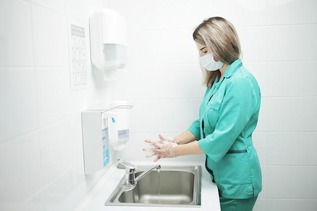 Een vrouwelijke arts in een beschermend masker en medisch uniform wast haar handen grondig in het ziekenhuis. gezeepte handen in schuim