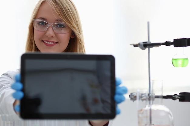 Een vrouwelijke arts in een chemisch laboratorium houdt