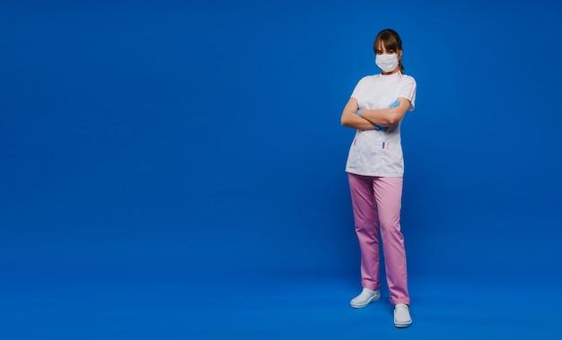 Een vrouwelijke arts in een medisch masker en handschoenen staat op een blauwe muur