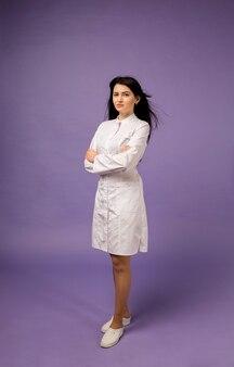 Een vrouwelijke arts in een medische toga van gemiddelde lengte staat op paars