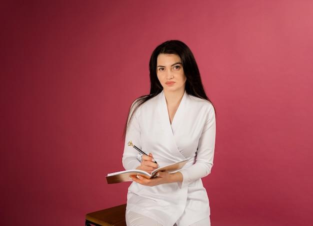 Een vrouwelijke arts in een medische witte jas zit met een pen en blocnote op rood