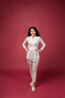 Een vrouwelijke arts in een wit medisch pak van gemiddelde lengte op bordeauxrood