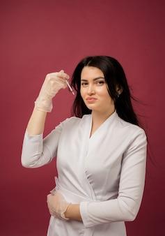 Een vrouwelijke arts in een wit pak houdt een spuit op bordeauxrood