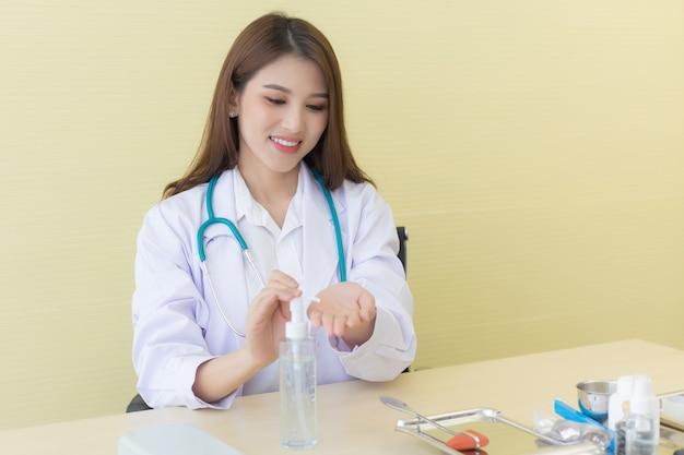 Een vrouwelijke arts in een witte laboratoriumjas zit en pompt de alcoholgel om haar handen schoon te maken tijdens het wachten