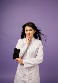 Een vrouwelijke arts in een witte medische jurk heeft een zwart masker op paars