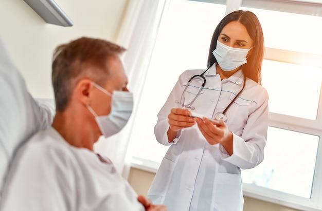 Een vrouwelijke arts met een beschermend medisch masker meet de temperatuur van een volwassen mannelijke patiënt die tijdens de coronavirus- of covid-19-epidemie revalidatie ondergaat in een moderne ziekenhuisafdeling.