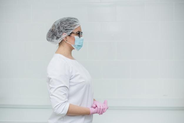 Een vrouwelijke arts met een bril, een wit medisch pak, een pet, een medisch masker en wegwerphandschoenen staat zijwaarts in het kantoor