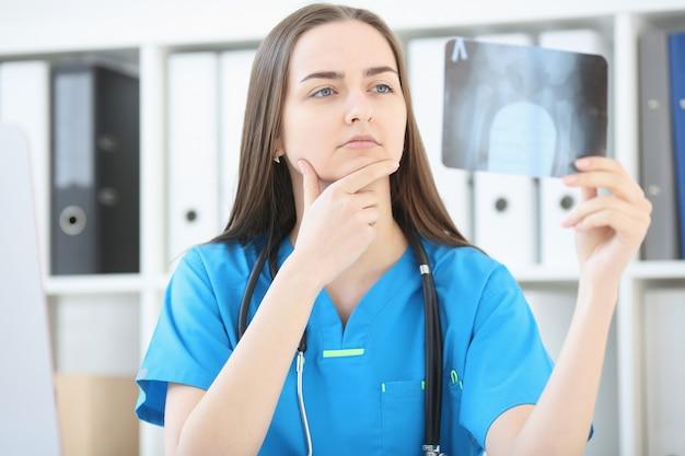 Een vrouwelijke arts met een serieuze blik onderzoekt een röntgenfoto