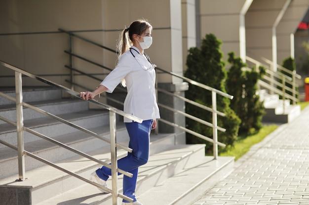 Een vrouwelijke arts of verpleegster die een beschermend masker en medische kleding draagt op de trappen van het ziekenhuis