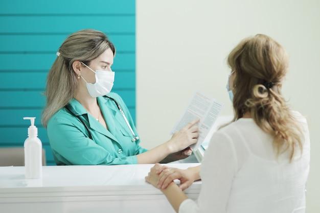 Een vrouwelijke arts of verpleegster die een medisch masker draagt, praat met een vrouwelijke patiënt in de wachtkamer van een ziekenhuis. desinfector op een rek