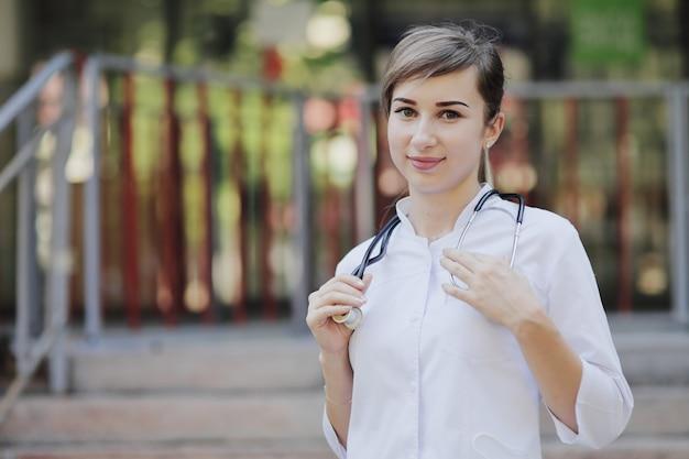 Een vrouwelijke arts of verpleegster in medisch uniform houdt een stethoscoop om haar nek