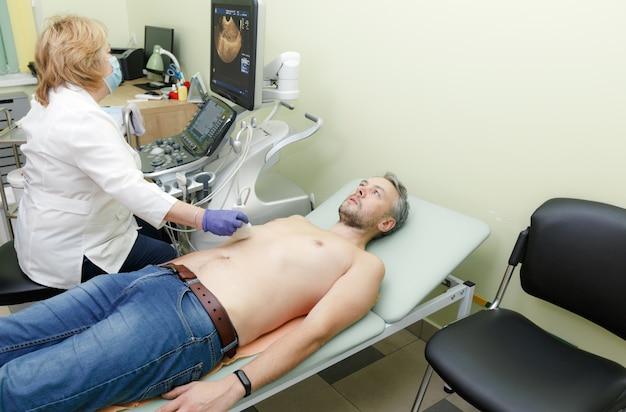 Een vrouwelijke arts onderzoekt een patiënt op een echografie-apparaat. moderne medische kliniek.