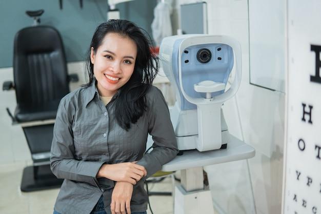 Een vrouwelijke arts poseren naast een oogtestkit in een onderzoekskamer bij de oogkliniek