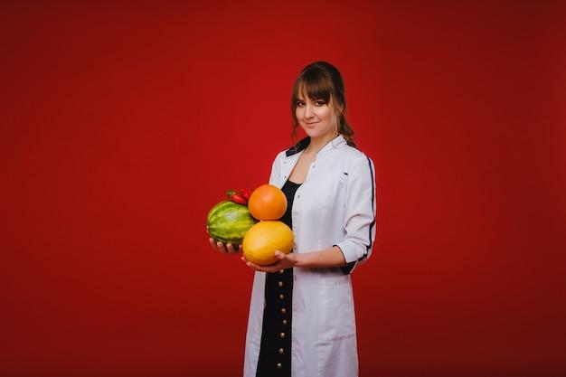 Een vrouwelijke arts-verpleegster in een witte jas met fruit in haar handen vormt op een rode achtergrond, meloen, watermeloen, aardbei en grapefruit.