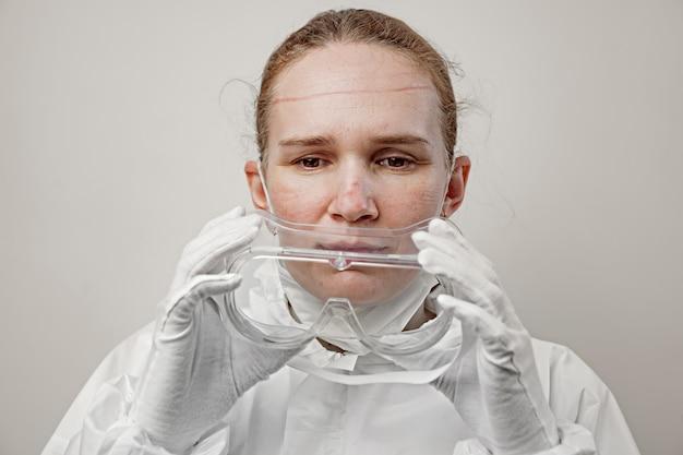 Een vrouwelijke arts verwijdert een beschermend pak, masker en bril na een dag werken in het ziekenhuis.