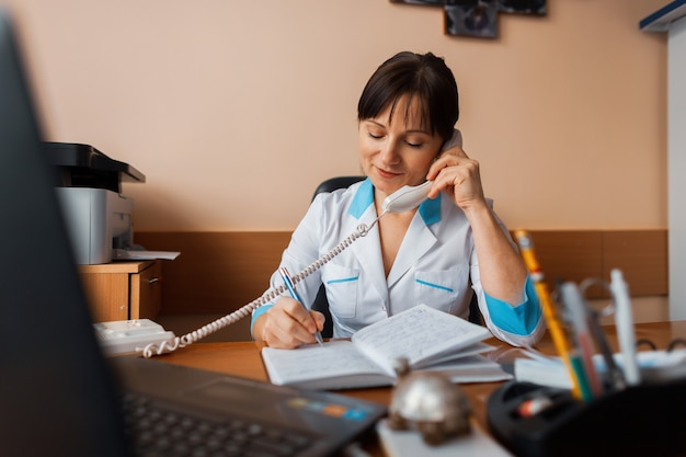 Een vrouwelijke arts zit aan haar bureau in een kantoor in een ziekenhuis, praat aan de telefoon en maakt aantekeningen in een notitieblok. de moderne geneeskunde.