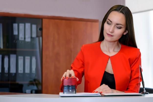 Een vrouwelijke baas in een felrood pak legt een zegel op het contract bij de receptie.