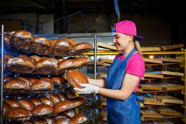Een vrouwelijke bakker is op de werkplek bij de bakkerij. een professionele bakker houdt brood in zijn handen. broodproductieconcept