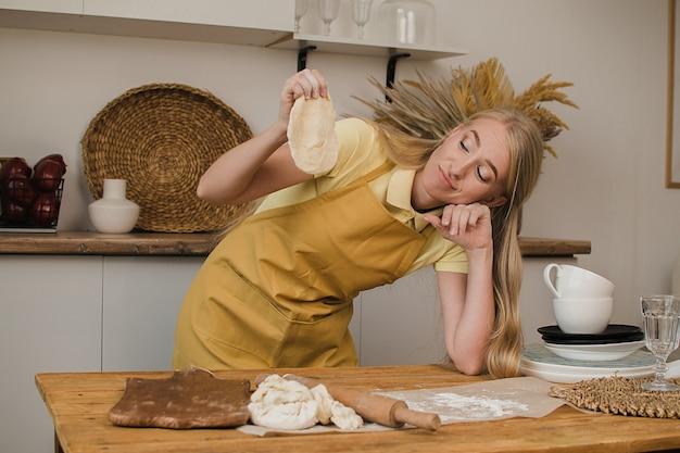 Een vrouwelijke bakker of huisvrouw kijkt naar het deeg en denkt na over wat te koken.