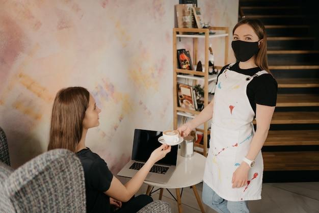 Een vrouwelijke barista in een zwart gezichtsmasker serveert een meisje een latte in een coffeeshop. een meisje met lang haar dat op afstand op een laptop werkt, houdt sociale afstand en bestelt een koffie in een café.