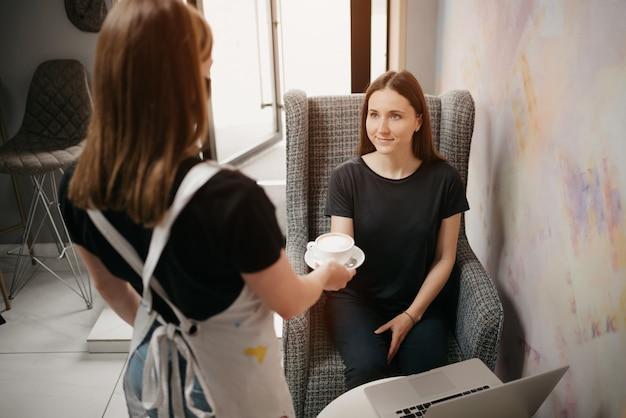 Een vrouwelijke barista in een zwart gezichtsmasker serveert een meisje een latte in een coffeeshop. een meisje met lang haar dat op afstand op een laptop werkt, houdt sociale afstand en neemt koffie van een serveerster in een café.
