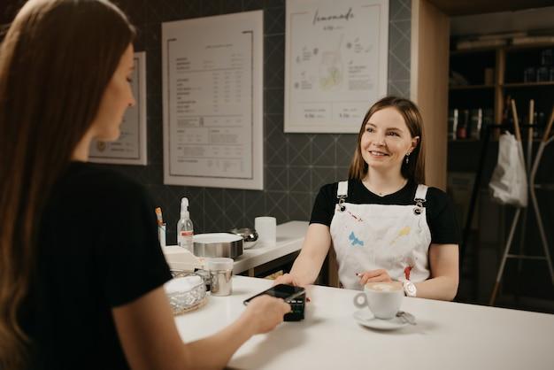 Een vrouwelijke barista lacht houdt een cliënt een terminal voor om te betalen voor een kopje koffie. een meisje met lang haar betaalt voor een latte met een smartphone door contactloze nfc-technologie in een café.