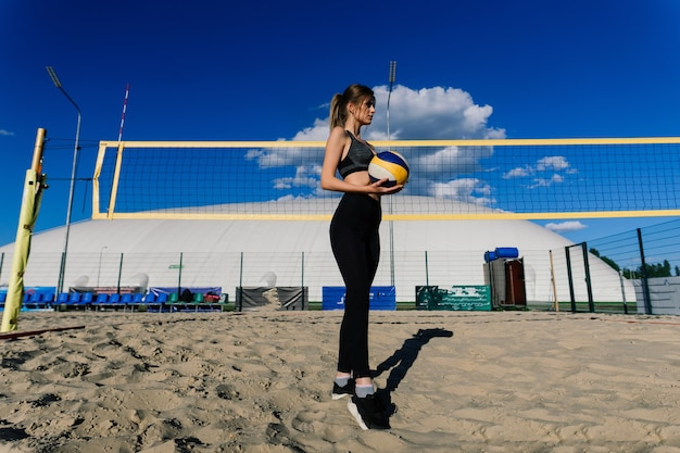 Een vrouwelijke beachvolleybalatleet met bal op het volleybalveld