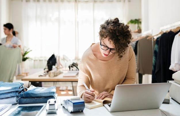Een vrouwelijke bedrijfseigenaar gebruikt laptop