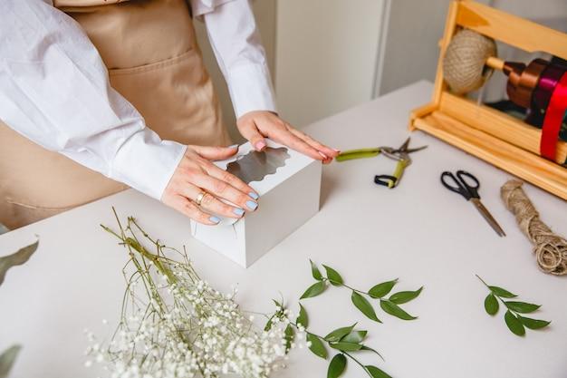 Een vrouwelijke bloemist maakt een geschenkdoos van wit papier op haar bureau in een bloemenwinkel