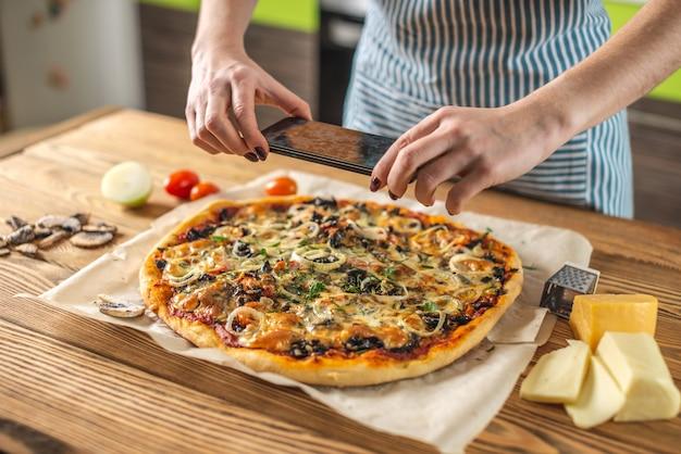 Een vrouwelijke blogger maakt foto's van zelfgemaakte pizza's op haar telefoon