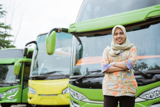 Een vrouwelijke busbemanning in een sluier glimlacht met gekruiste handen tegen de busvloot