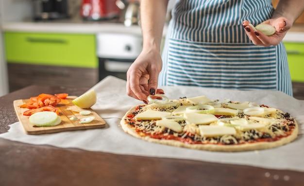 Een vrouwelijke chef-kok in een schort legt uienringen op een rauwe pizza