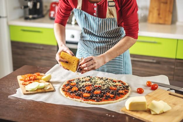 Een vrouwelijke chef-kok in een schort wrijft kaas op een rauwe pizza