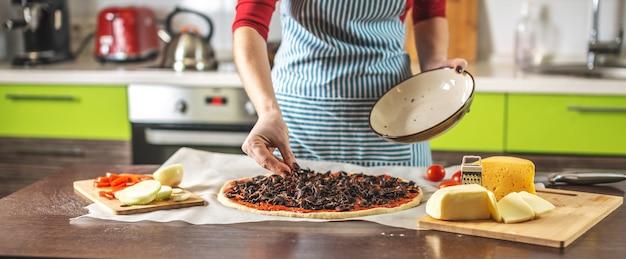 Een vrouwelijke chef-kok in een schort zet champignons op een rauwe pizza