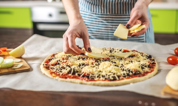 Een vrouwelijke chef-kok in een schort zet mozzarellakaas op een rauwe pizza
