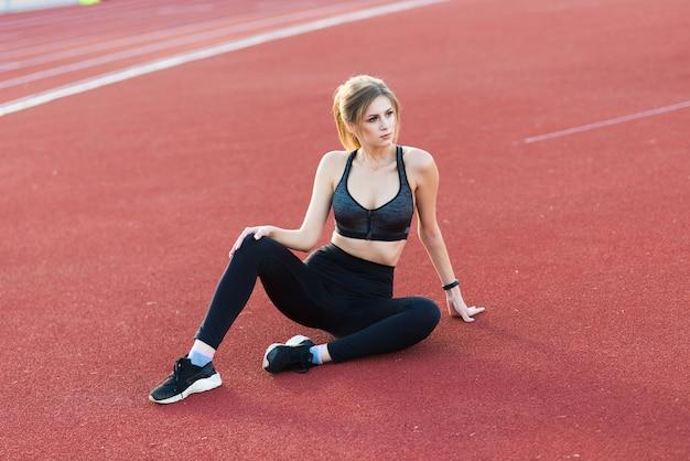 Een vrouwelijke coach met donker haar staat op de rode atletiekbaan van het stadion, gekleed in sportuniform.