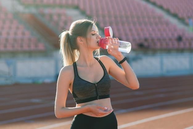 Een vrouwelijke coach met donker haar staat op de rode atletiekbaan van het stadion