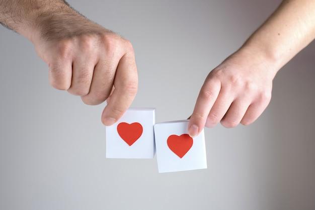 Een vrouwelijke en een mannelijke handen met twee witte dozen met rode harten, close-up