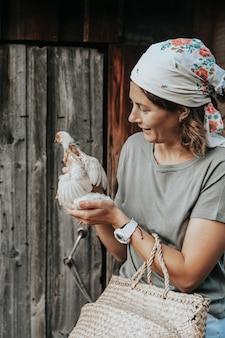 Een vrouwelijke gastvrouw zorgt voor de pasgeboren gele kippen in haar tuin. klein huis boerderij en kinderboerderij concept