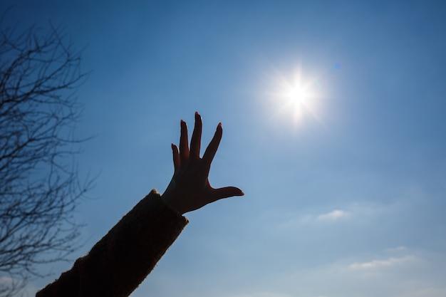 Een vrouwelijke hand afgetekend tegen een blauwe lucht en een felle zon