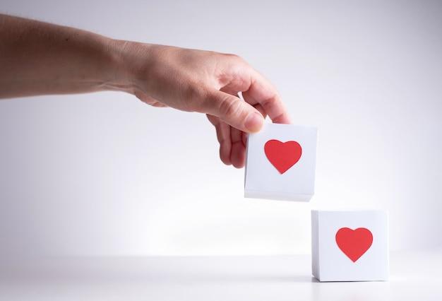 Een vrouwelijke hand brengt een witte doos met een rood hart naar een andere rode doos met een rood hart, close-up.