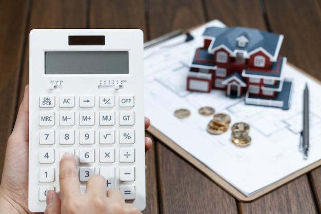 Een vrouwelijke hand die een rekenmachine voor een villa-huismodel gebruikt