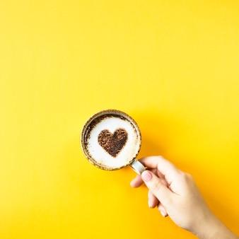 Een vrouwelijke hand houdt een kop koffie waarop een hart wordt getrokken