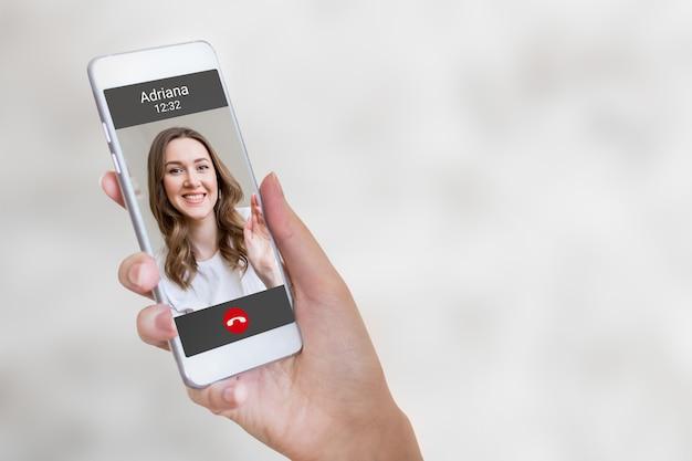 Een vrouwelijke hand houdt een mobiele telefoon vast met een meisje op het scherm, videochat. een vrouw voert een videogesprek met haar vriend. gelukkig jong meisje glimlacht op een telefoonscherm, interface, belknop. ruimte kopiëren