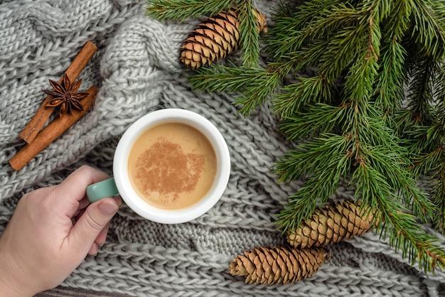 Een vrouwelijke hand houdt een mok met koffie met melk en kaneel met dennentakken en kegels. wintersamenstelling met dennentakken, een deken en een mok met cacao.