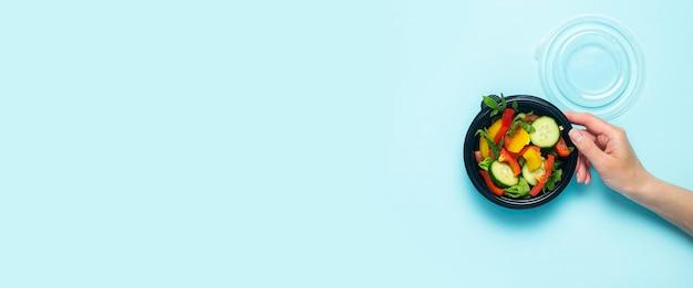 Een vrouwelijke hand houdt een open plastic wegwerpbord met groentesalade op een lichtblauwe achtergrond. bovenaanzicht, plat gelegd. banier.