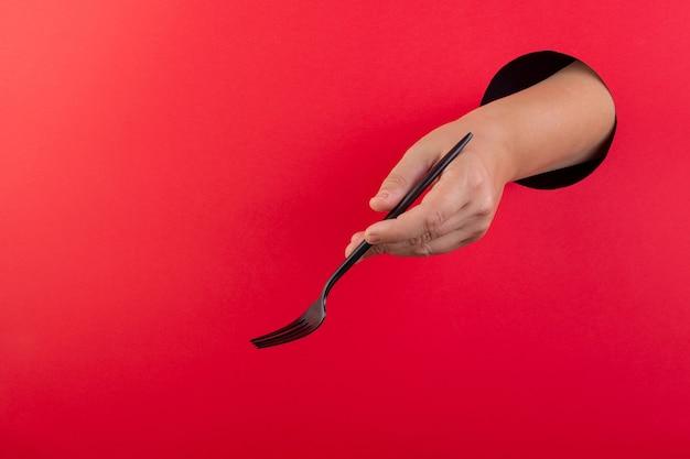 Een vrouwelijke hand houdt zwart bestek op een rode achtergrond. sjabloon voor ontwerp. ruimte voor tekst.