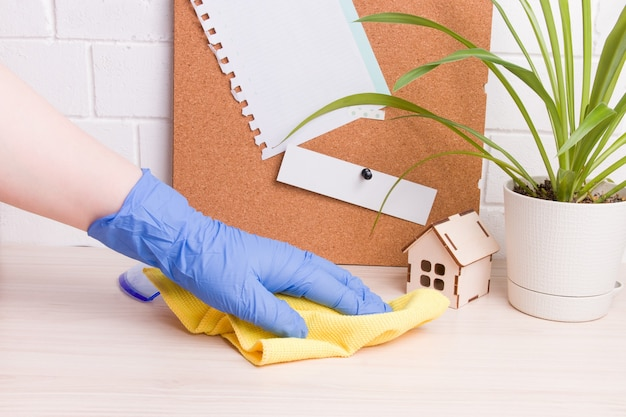 Een vrouwelijke hand in een blauwe rubberen handschoen veegt een bureaublad af met een gele doek, een bloem in een pot en een kurkbord