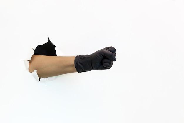 Een vrouwelijke hand in een zwarte latexhandschoen door gescheurd papier op een witte achtergrond toont een vuist quarantin